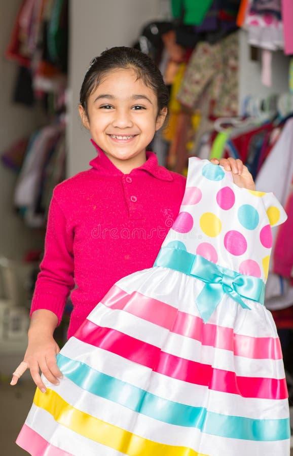 Menina que selecciona um vestido do armário fotos de stock