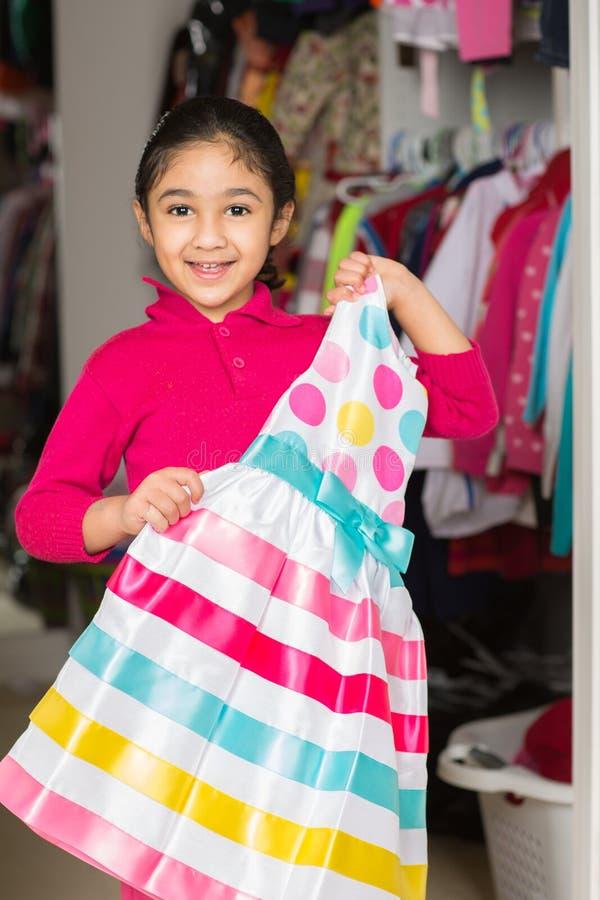 Menina que selecciona um vestido do armário imagens de stock royalty free