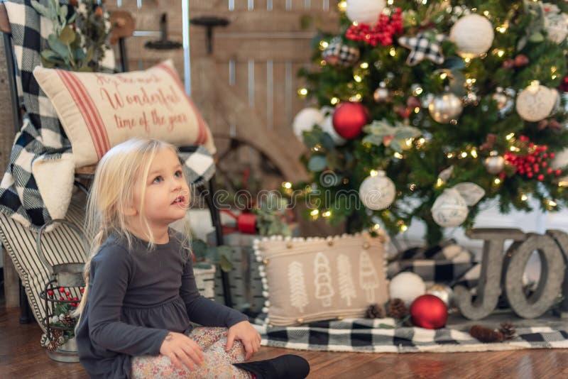 Menina que senta-se ao lado da árvore de Natal foto de stock