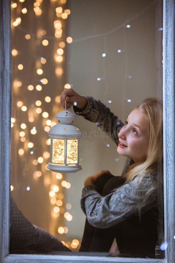Menina que senta-se ao lado da janela imagens de stock royalty free