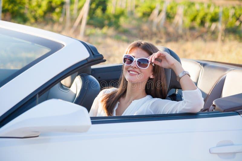 A menina que senta-se atrás da roda de um convertible branco foto de stock royalty free