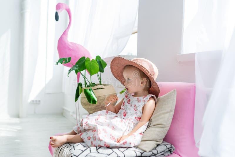 Menina que senta-se com o pirulito no treinador na sala de visitas em casa com chapéu imagens de stock royalty free