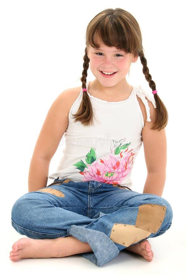 Menina que senta-se com os pés descalços no assoalho branco imagens de stock royalty free