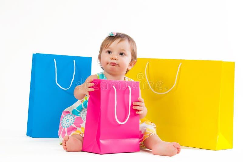 Menina que senta-se com os sacos de papel coloridos isolados no fundo branco fotos de stock royalty free