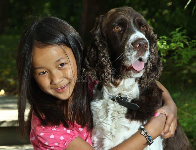 Menina que senta-se com seu cão fotos de stock