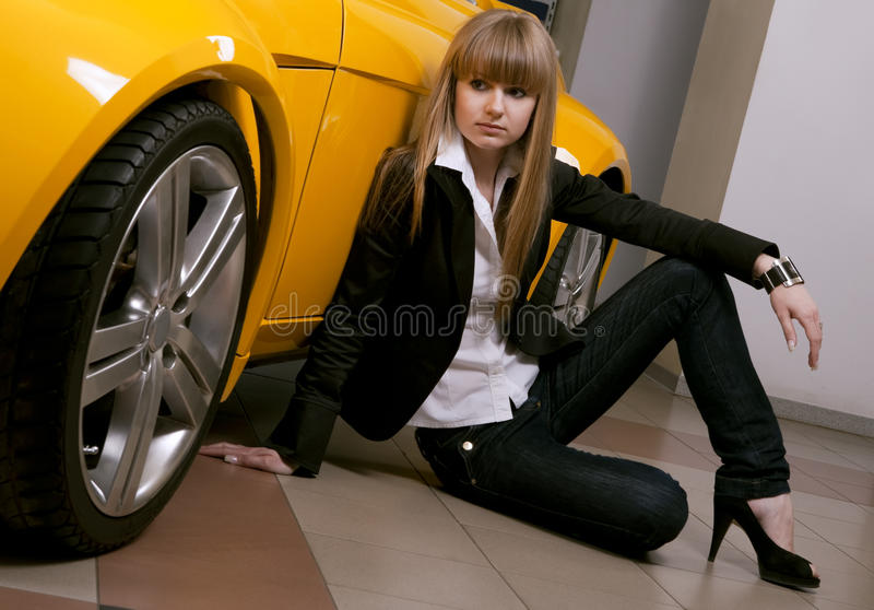 Menina que senta-se de encontro do carro amarelo fotos de stock royalty free