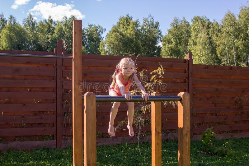 Menina que senta-se em barras paralelas fora imagem de stock