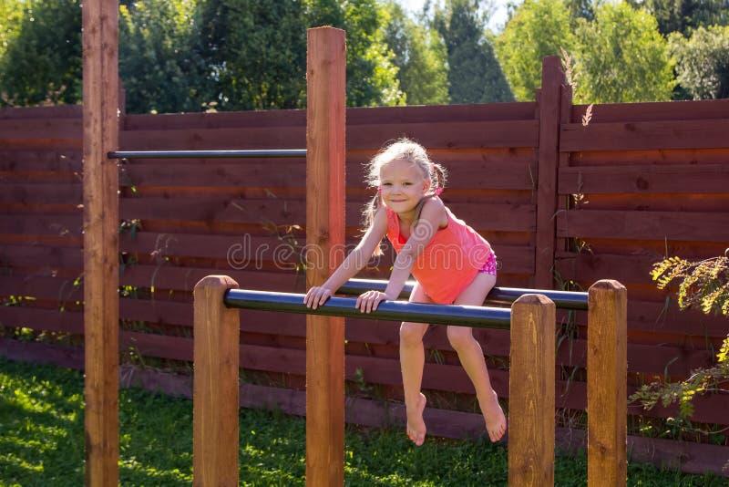 Menina que senta-se em barras paralelas fora fotografia de stock