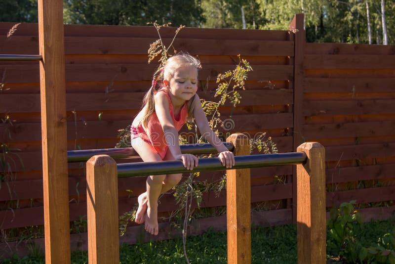 Menina que senta-se em barras paralelas fora fotos de stock