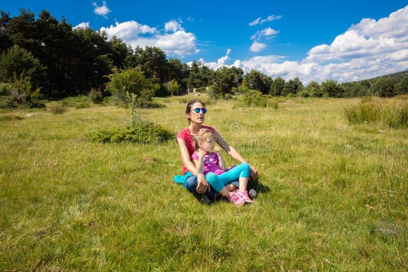 Menina que senta-se em sua mãe em um prado da grama do país no Madri imagem de stock royalty free