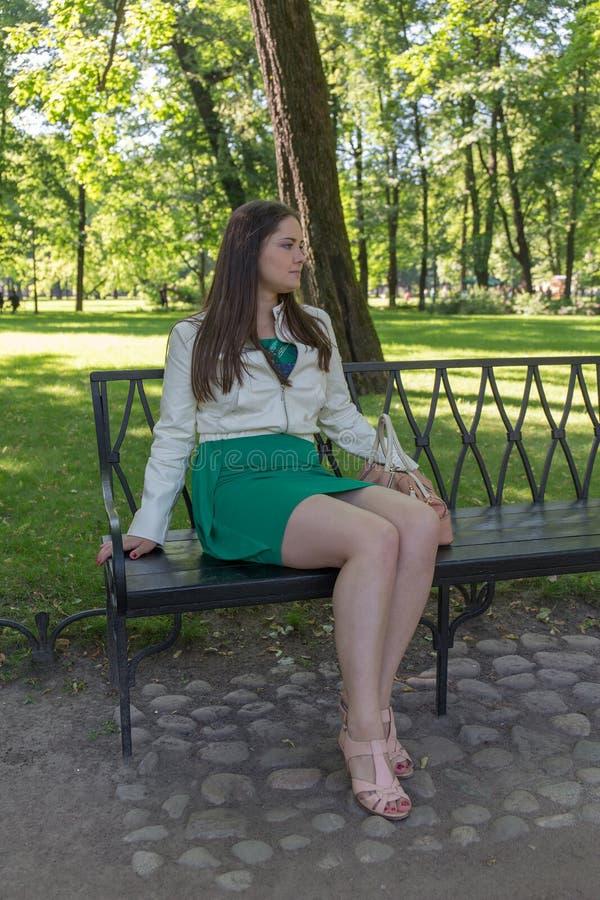 Menina que senta-se em um banco foto de stock