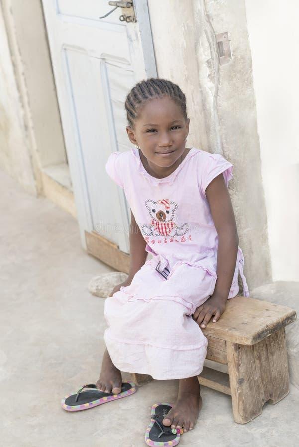 Menina que senta-se em um banco, 6 anos do Afro velho fotos de stock