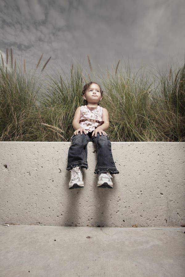 Menina que senta-se em um banco de parque fotos de stock