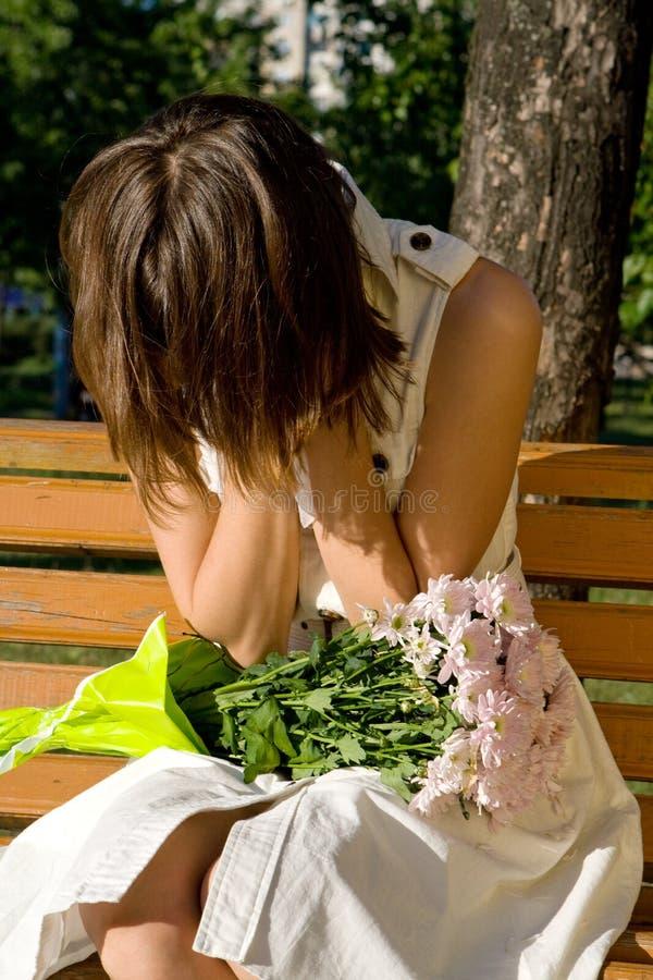 Menina que senta-se em um banco em um grito do parque imagem de stock