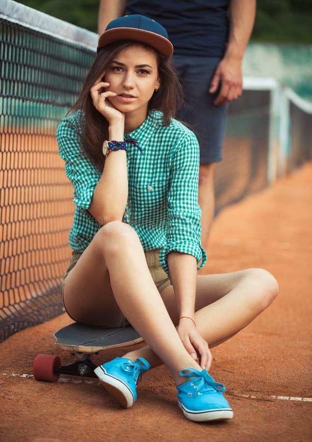 Menina que senta-se em um skate no campo de tênis fotos de stock royalty free