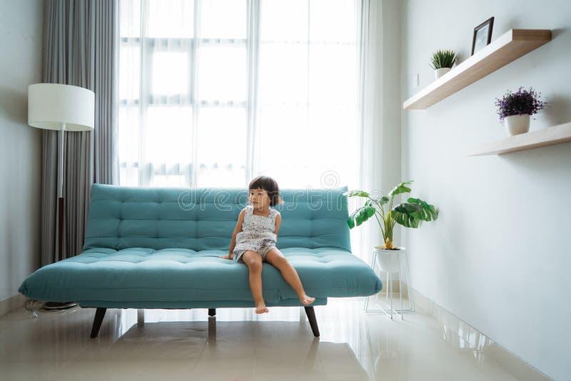 Menina que senta-se em um sof? confort?vel fotografia de stock royalty free
