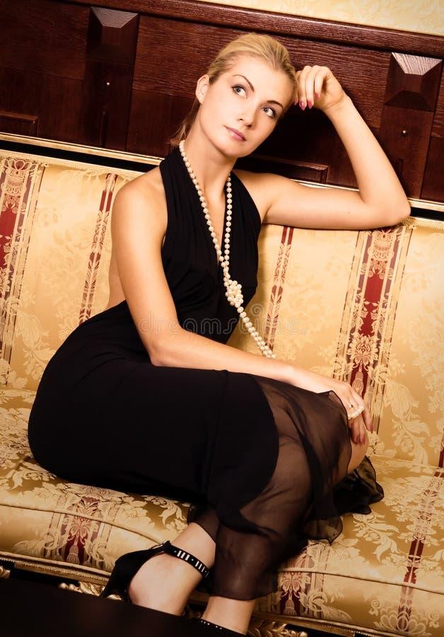 Menina que senta-se em um sofá luxuoso fotografia de stock