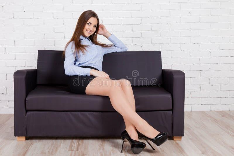 Menina que senta-se em um sofá preto foto de stock