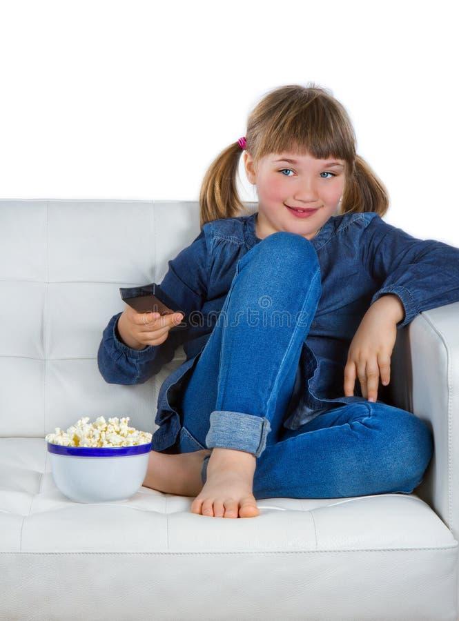 Menina que senta-se em um sofá que presta atenção à tevê imagem de stock
