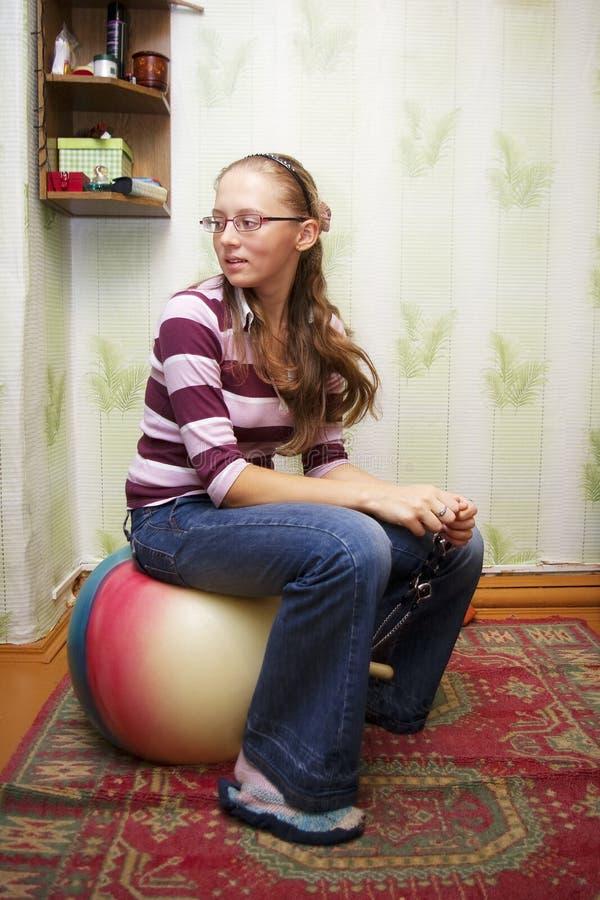 Menina que senta-se em uma bola grande imagens de stock