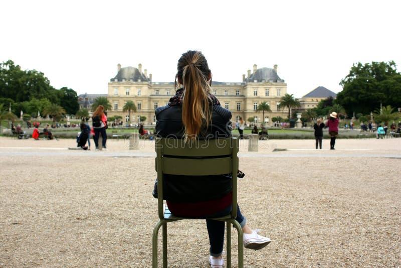 Menina que senta-se em uma cadeira que olha um tiro da parte traseira da construção pública imagens de stock royalty free