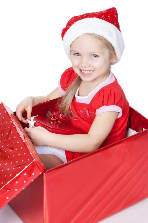 Menina que senta-se em uma caixa de Natal sobre o branco fotos de stock royalty free