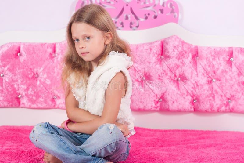 Menina que senta-se em uma cama cor-de-rosa fotos de stock