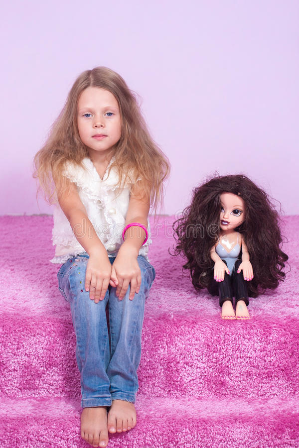 Menina que senta-se em uma cama cor-de-rosa com boneca fotografia de stock royalty free