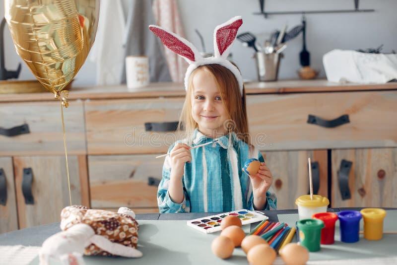 Menina que senta-se em uma cozinha imagem de stock