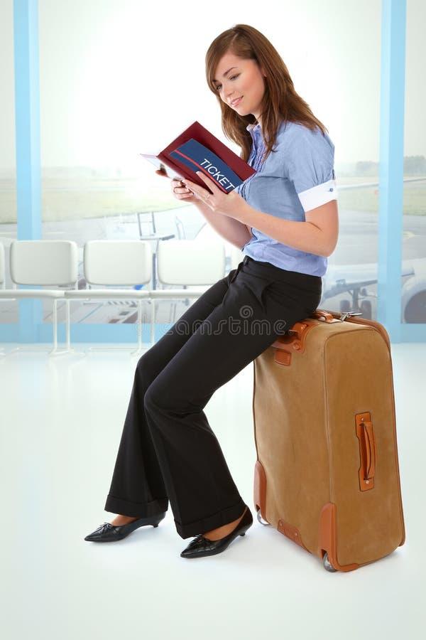 Menina que senta-se em uma mala de viagem fotografia de stock