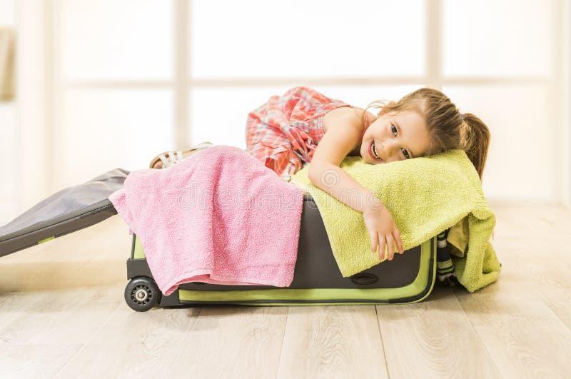 A menina que senta-se em uma mala de viagem, apronta-se para o curso foto de stock
