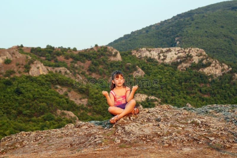 Menina que senta-se em uma parte superior da montanha imagem de stock royalty free
