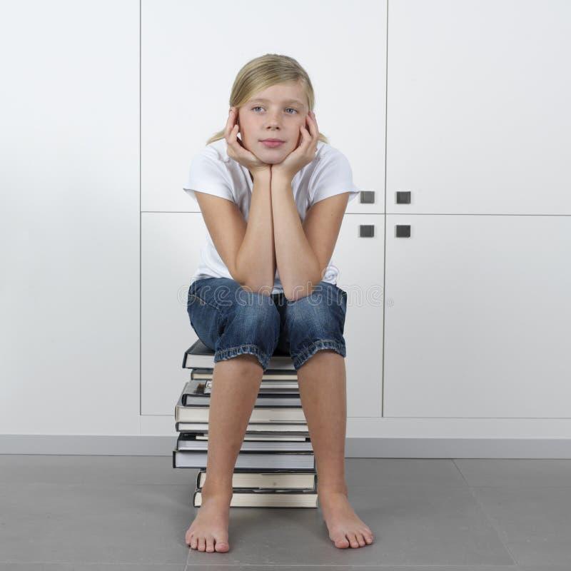 Menina que senta-se em uma pilha de livros imagens de stock royalty free