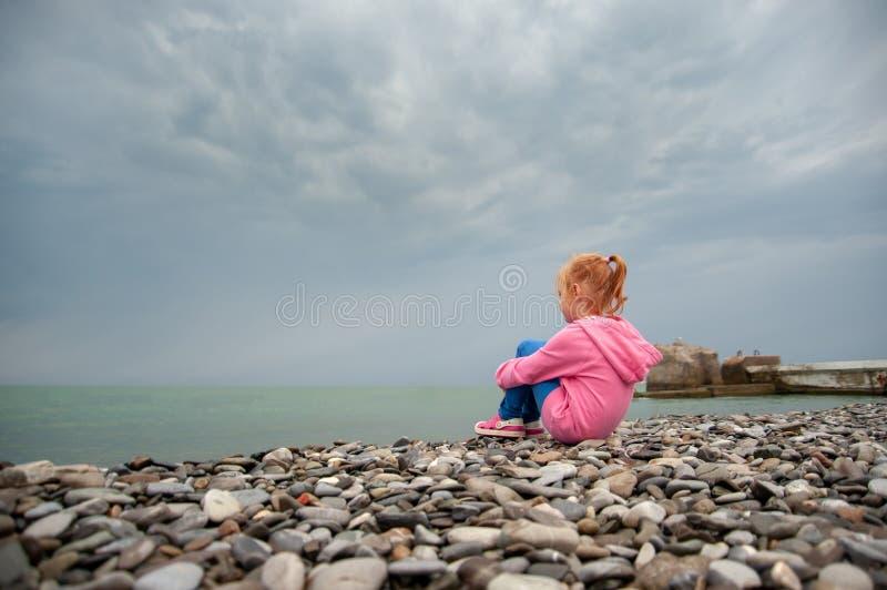 Menina que senta-se em uma praia rochosa com joelhos imagem de stock royalty free