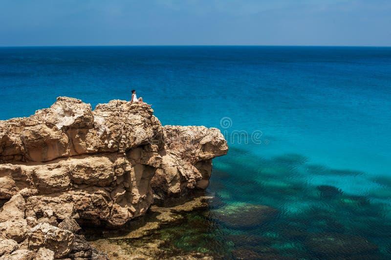 Menina que senta-se em uma rocha pelo mar foto de stock royalty free