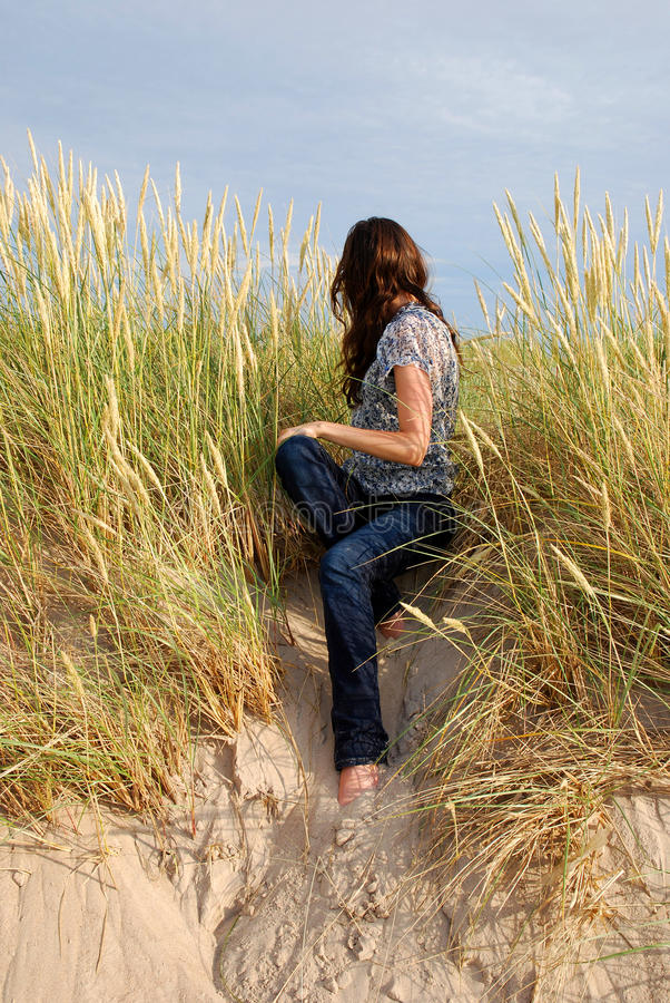 Menina que senta-se entre a grama fotografia de stock