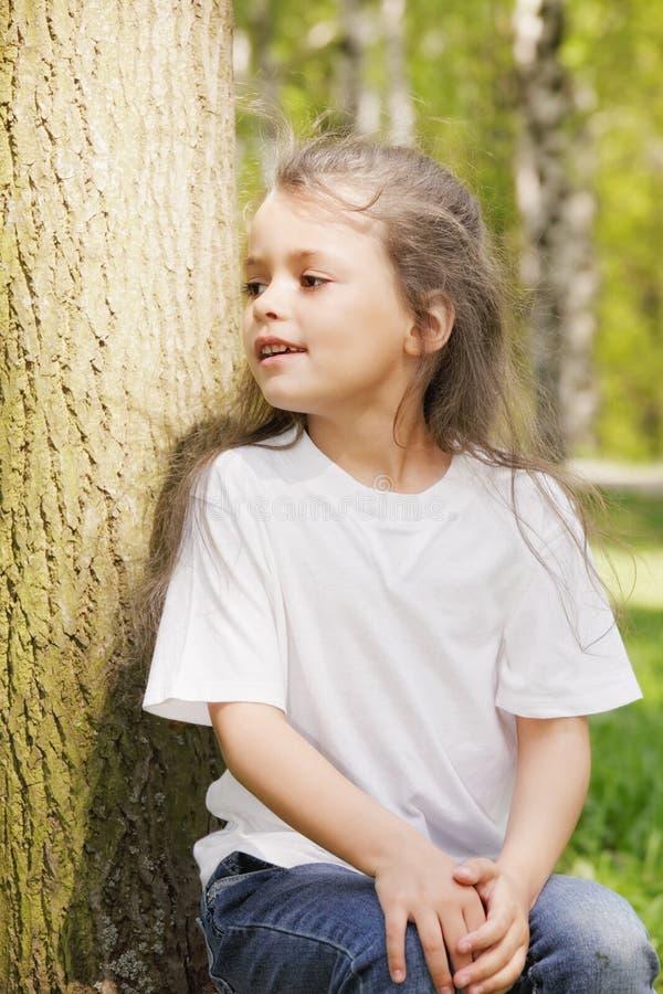 Menina que senta-se na árvore fotografia de stock royalty free