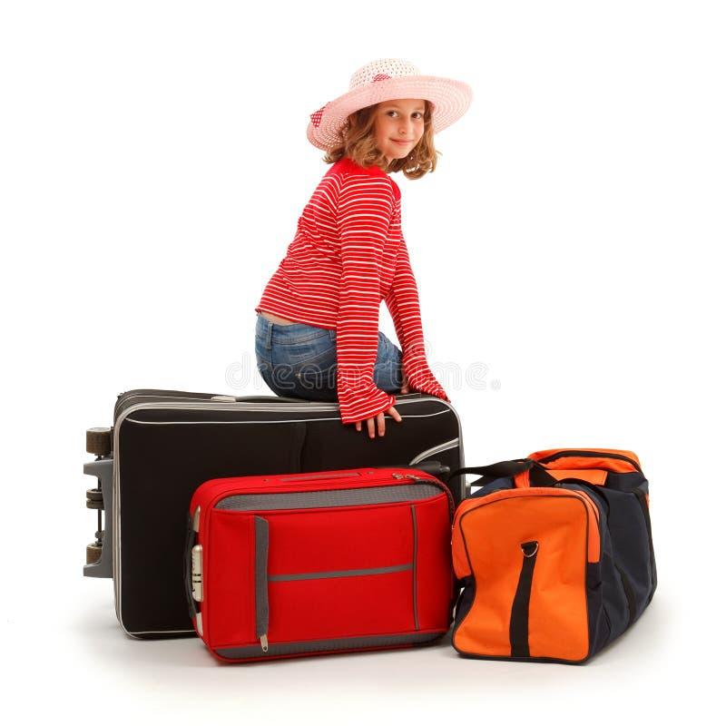 Menina que senta-se na bagagem fotografia de stock royalty free