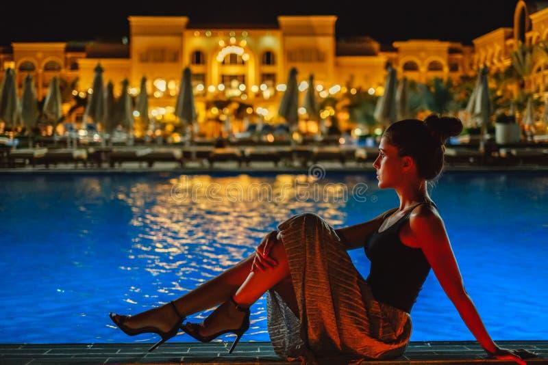 Menina que senta-se na borda da associação na noite fotos de stock