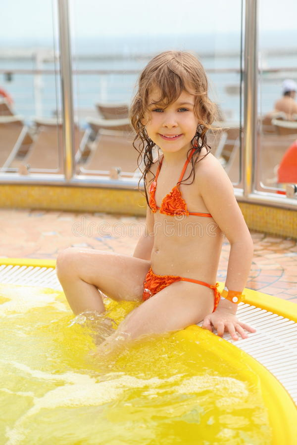 Menina que senta-se na borda da piscina imagem de stock
