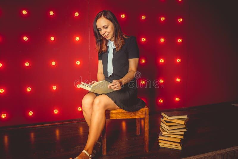 menina que senta-se na cadeira e que lê um livro fotografia de stock royalty free