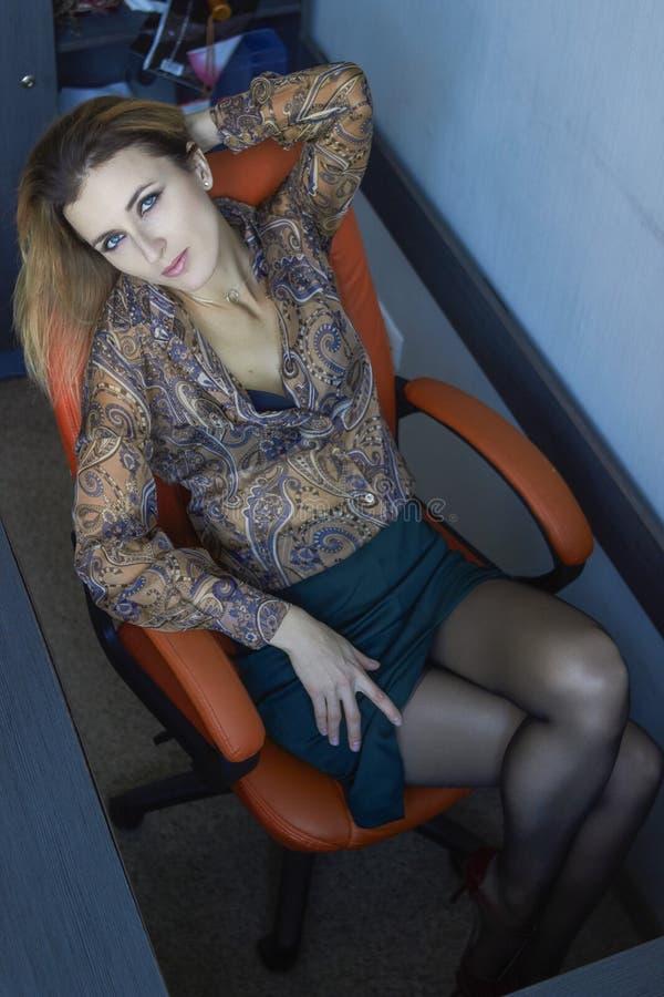Menina que senta-se na cadeira na opinião do escritório de cima de imagens de stock royalty free