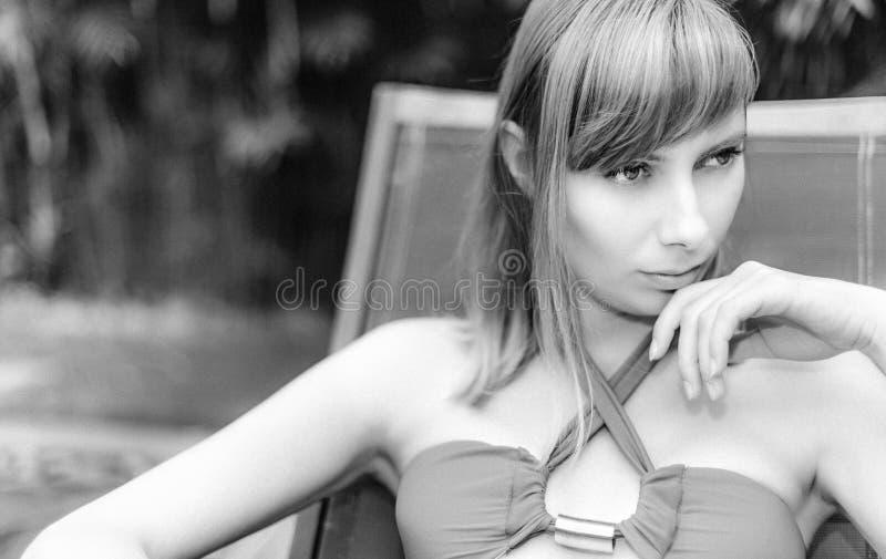 Menina que senta-se na cadeira, olhando pensativamente de lado imagem de stock royalty free