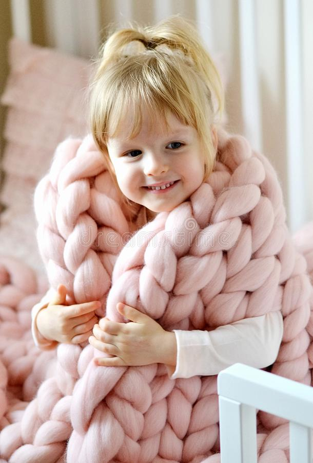 Menina que senta-se na cama com uma manta gigante feita malha fotos de stock