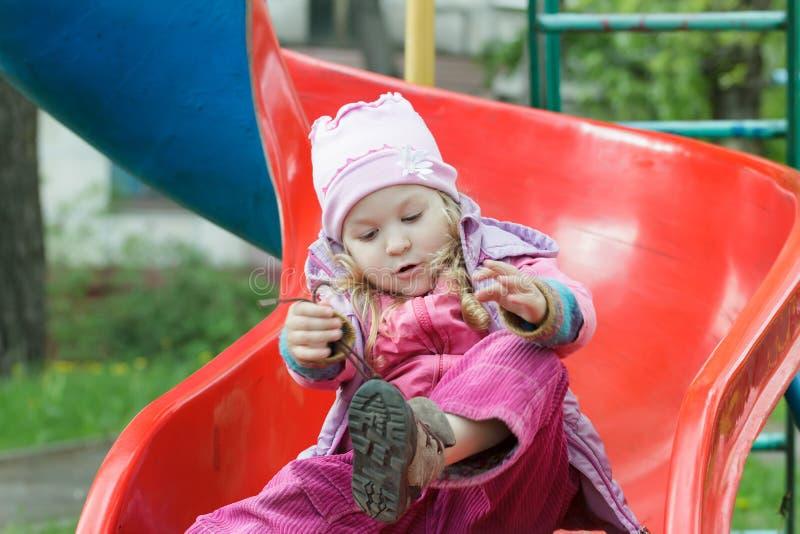 Menina que senta-se na corrediça plástica vermelha do campo de jogos e que amarra laços de seus instrutores das crianças imagem de stock royalty free
