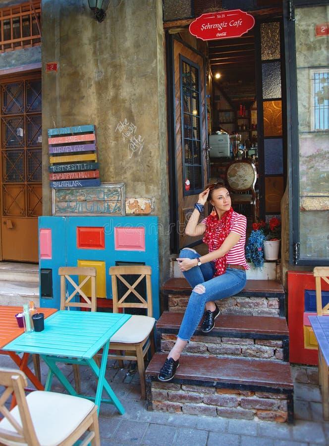 Menina que senta-se na entrada do café colorido em Balat que é uma vizinhança histórica imagem de stock royalty free