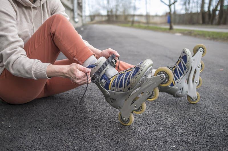 Menina que senta-se na estrada e que amarra os laços nos patins de rolo, c fotografia de stock