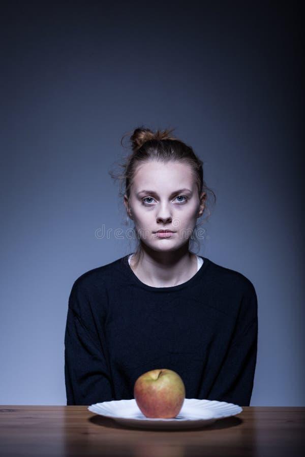 Menina que senta-se na frente da maçã imagem de stock royalty free