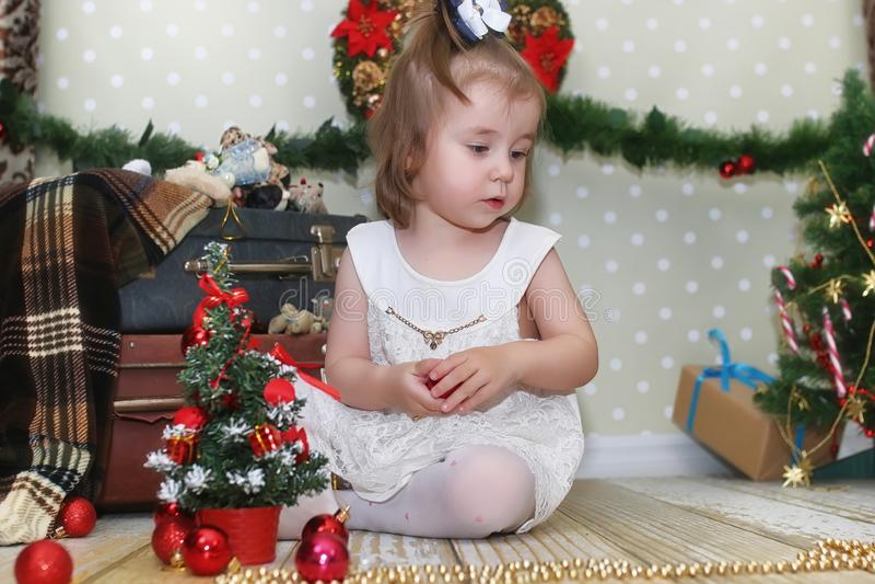 Menina que senta-se na frente de uma árvore de Natal imagem de stock royalty free