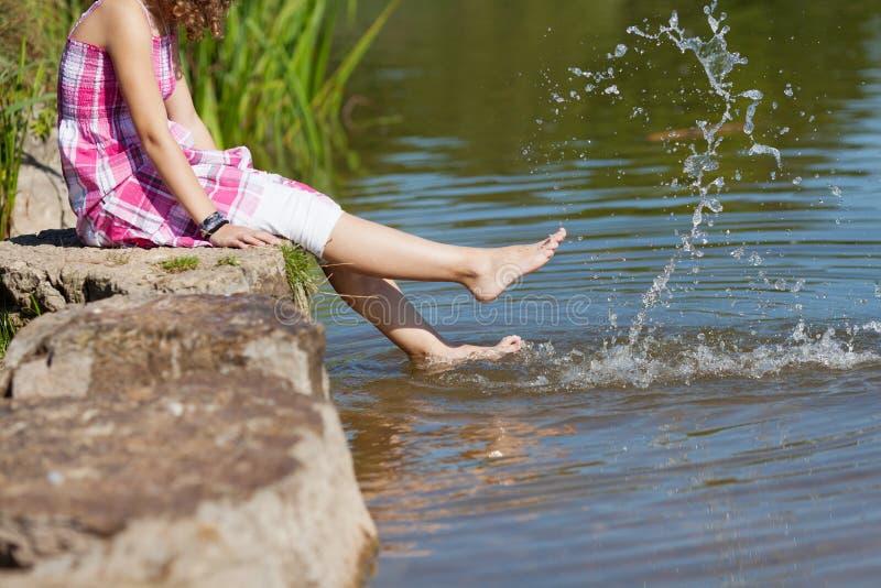 Menina que senta-se na rocha ao espirrar a água imagem de stock